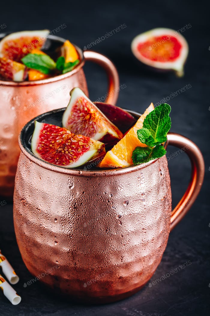 Fig moscow mule ice cold cocktail in copper cup with oranges and mint