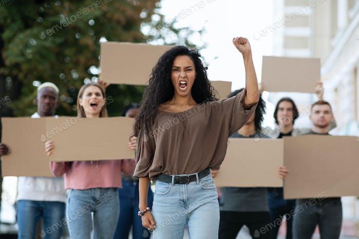 Mujer joven liderando un grupo de manifestantes en la calle