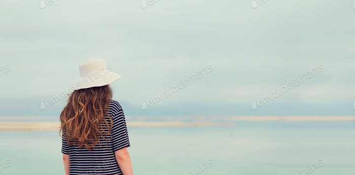 Woman in sailor striped dress near seaside of Dead Sea beach. Travel, summer vacation, holiday