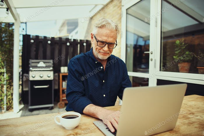Smiling senior man drinking coffee and using a laptop