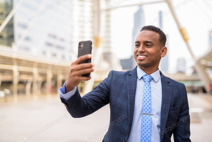 Happy young handsome African businessman taking selfie in the city outdoors