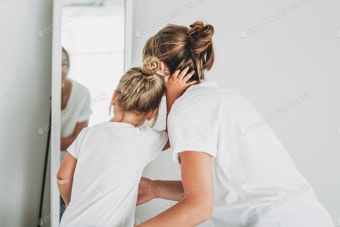 Young mother and daughter in white t-shirts look in mirror