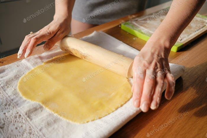 Frau rollt den Teig mit einem Nudelholz in den Sonnenstrahlen