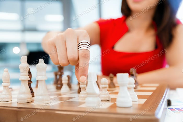 Business woman sitting in front of chess