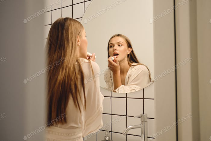 Young gorgeous girl in white dress dreamily looking in mirror applying lipstick in bathroom