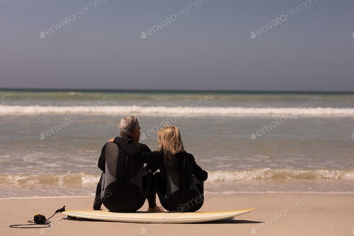 Rear view of senior couple sitting on surfboard at beach in the sunshine