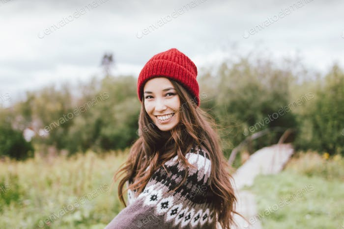 Beautiful carefree long hair asian girl in red hat and knitted nordic sweater in autumn nature park