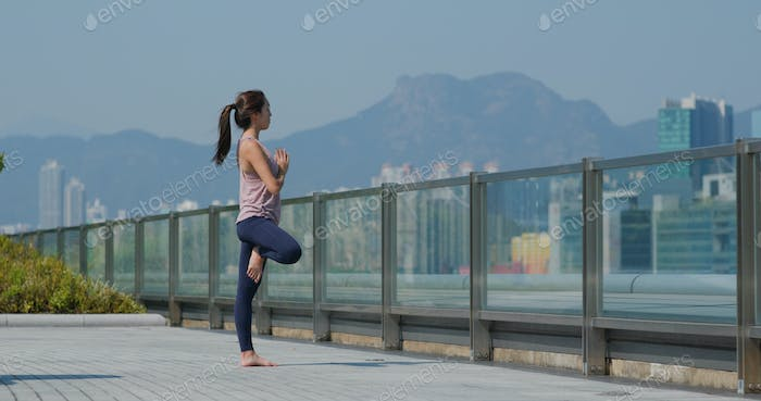 Woman do yoga at outdoor city
