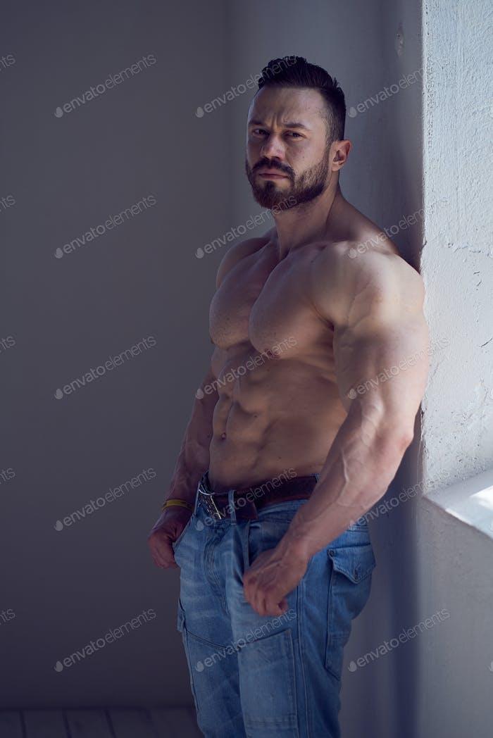 Bodybuilder male model in a jeans near window.