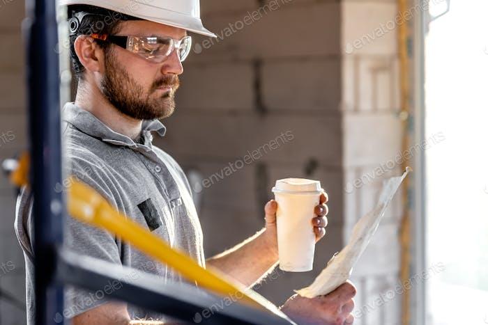Un manitas examina un dibujo en una obra de construcción.