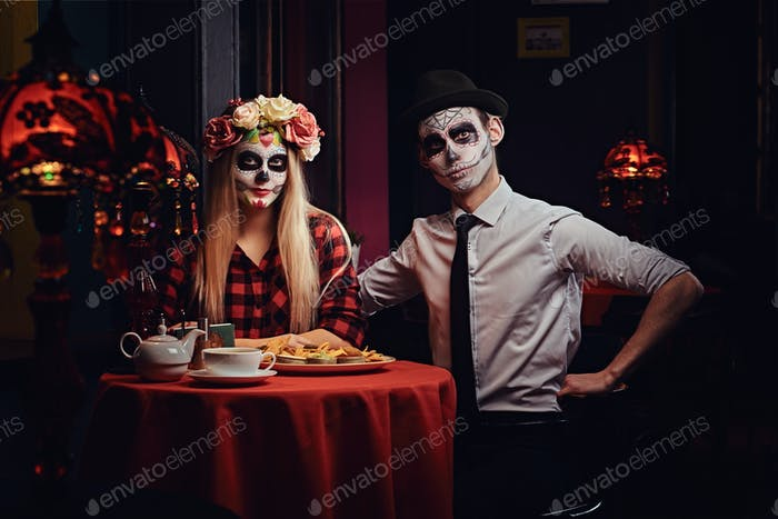 Young attractive couple with undead makeup eating nachos during dating at a mexican restaurant.