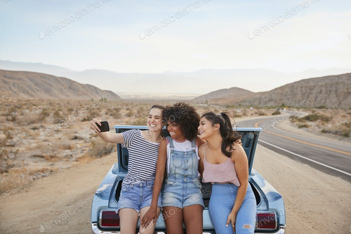 Three Female Friends Posing For Selfie Sitting In Trunk Of Classic Car On Road Trip