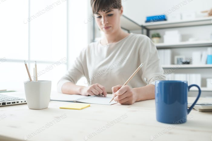 Junge Frau skizziert auf einem Notizbuch