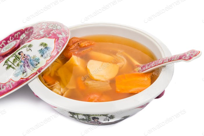 Casserole of Chinese potatoes carrots and tomatoes soup isolated in white