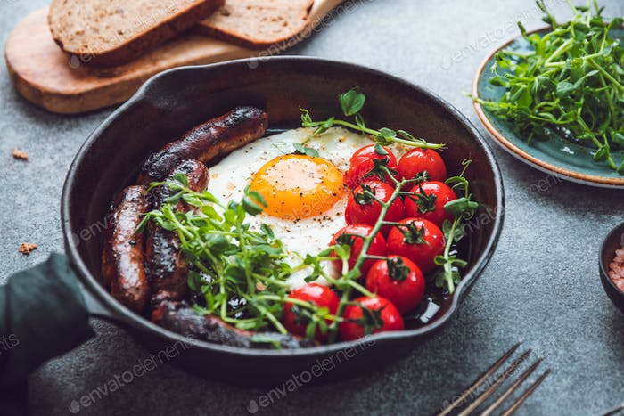 Breakfast time, fried egg with sausages and cherry tomatoes