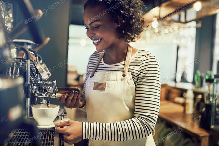 Smiling young African barista preparing coffee in a cafe