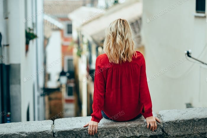 Young blonde tourist woman sitting outdoors looking a beautiful