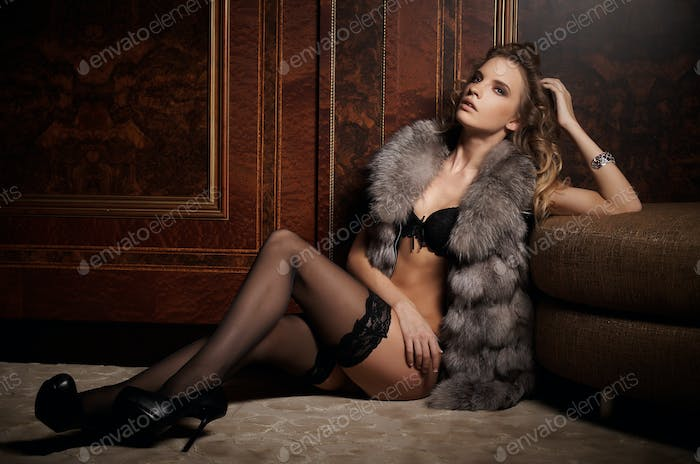 Woman in fur coat sitting on the floor.