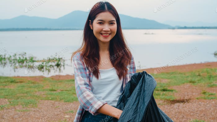 Portrait of young Asia lady volunteers help to keep nature clean up on the beach.