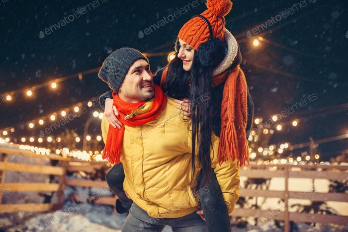 Winter evening, love couple having fun outdoors