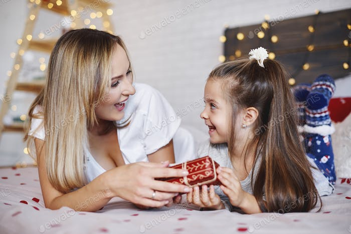 Girl giving christmas present to her mom