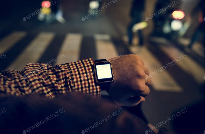 Arm with digital wrist watch at night time