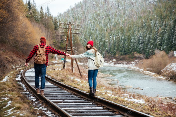Couple walking on old railroad in mountains