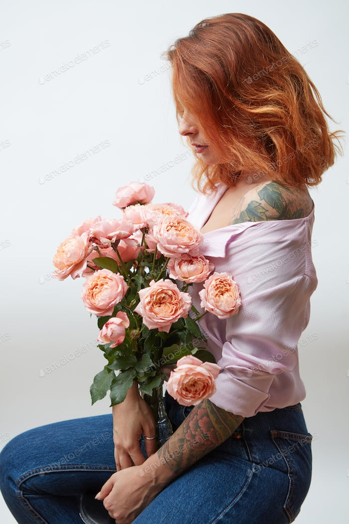 A vase with a bouquet of pink roses is being held by a girl with a tattoo around a gray background
