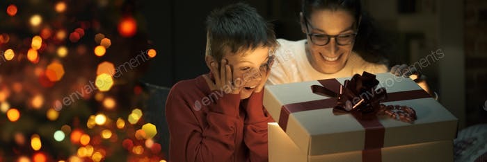 Boy and his mom opening a beautiful Christmas gift