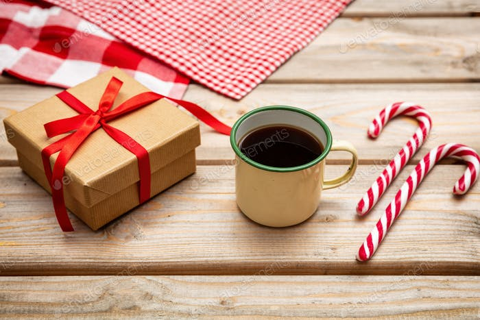 Cup of coffee with candy canes and a gift box with red ribbon on wooden background