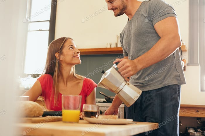 Mann serviert Frühstück zu seiner Freundin