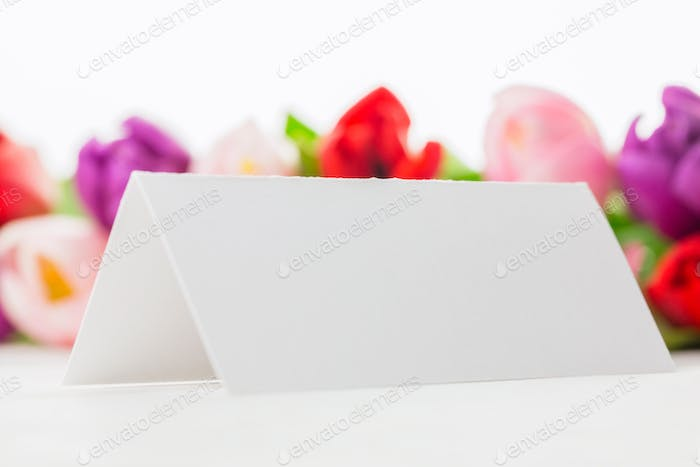 Close up of colorful tulips and white card on wooden table
