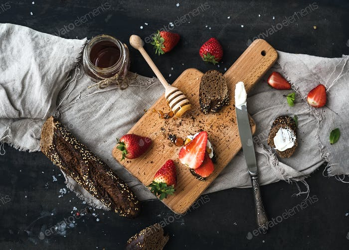 Breakfast set. Black baguette toasts with fresh strawberries, honey and mascarpone cheese