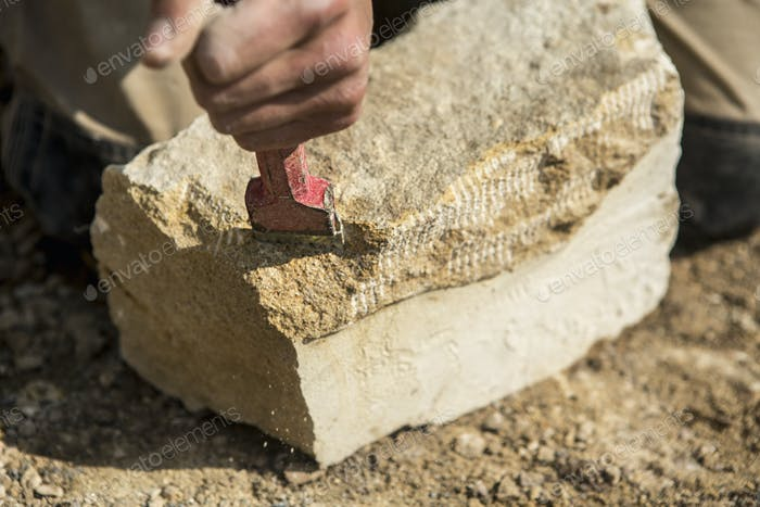 Construction worker holding a chisel, working on a stone.