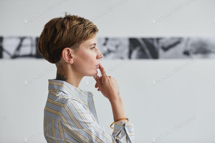 Pensive Zeitgenössische Frau Blick auf Kunst