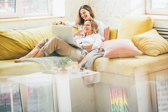Girlfriends relaxing on colorful sofa in modern interior with rainbow flag on window.