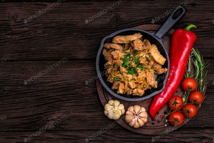 Cerdo frito en sartén y verduras