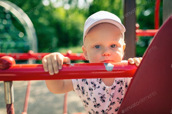 Baby boy playing in playground alone.