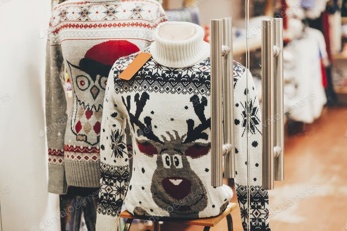Weihnachtspullover mit Rentier und Eule im Fenster des Ladens in der europäischen Stadtstraße