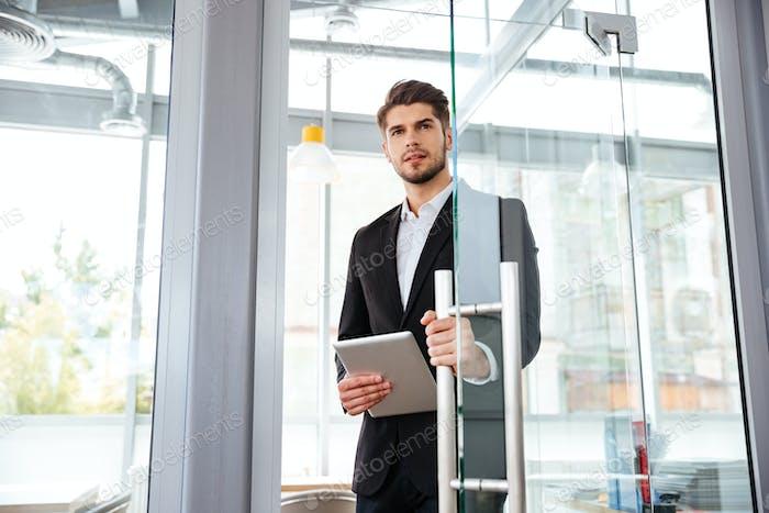 Бизнесмен с планшетом, входящим в дверь в офис