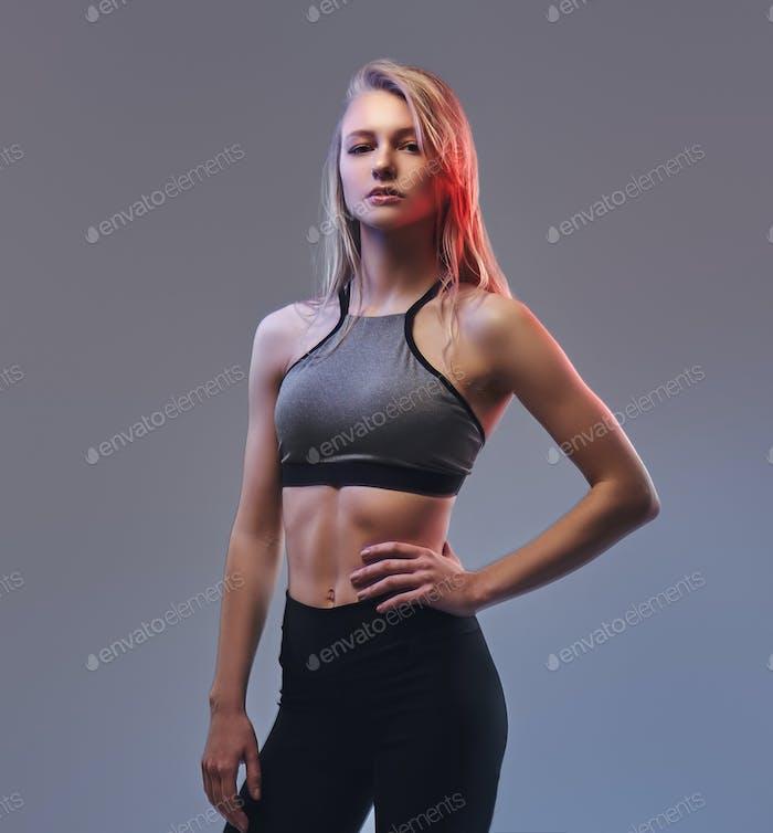 Sexy schlanke blonde Mädchen in einer Sportbekleidung posiert in einem Studio.