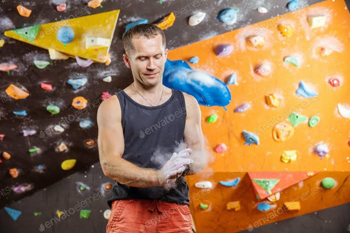Rock climber putting chalk on hands