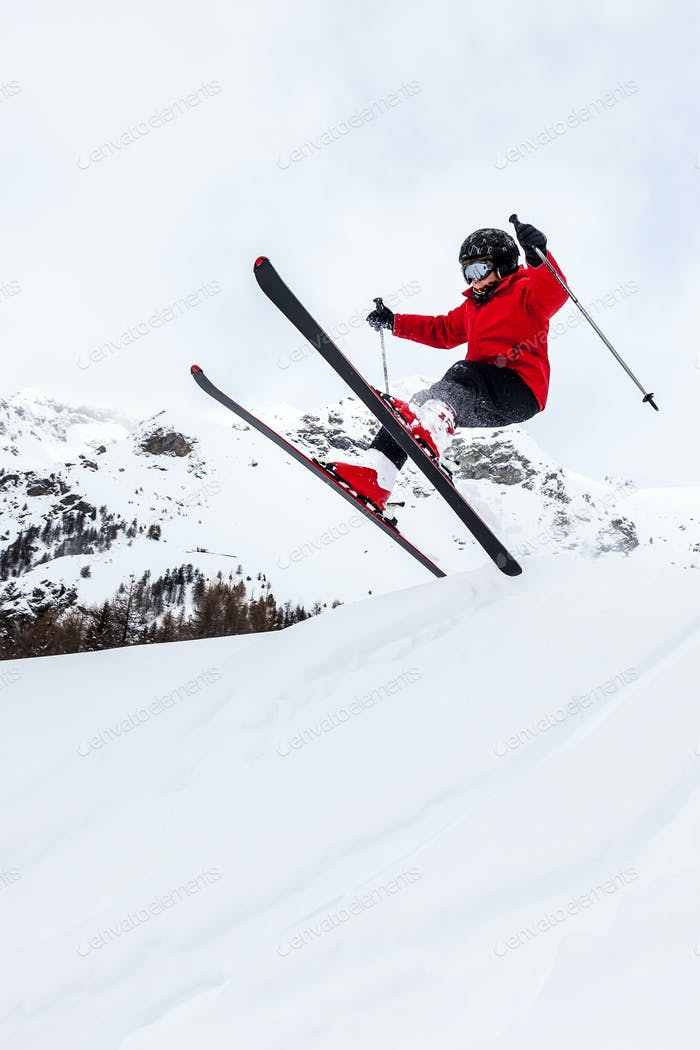 Male kid performs a high jump with the ski. Winter season, red jacket. Valle d'Aosta, Italy, Europe.