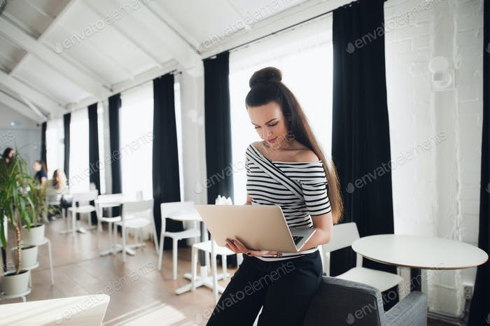 Smiling Attractive Woman Working on Laptop in Cafe.