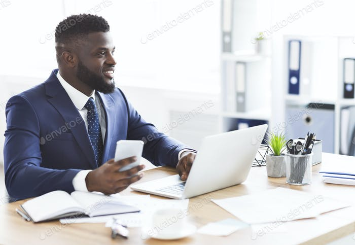 Happy businessman surfing internet on phone, working in office