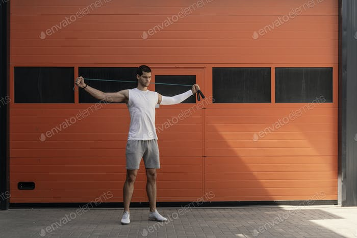 Portrait of muscular young man exercising, stretching with jumpi