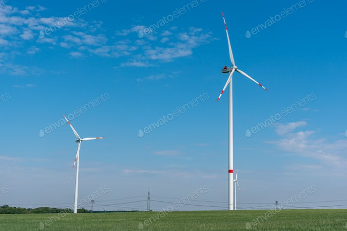 Modern wind energy turbines in a cornfield