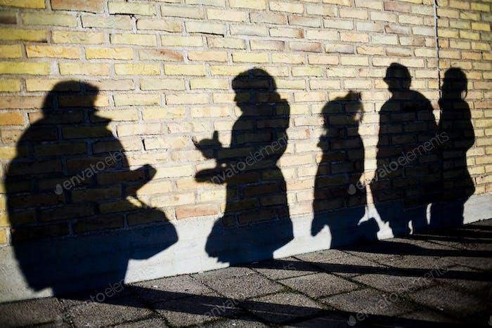 Schatten von Freunden auf der umliegenden Mauer auf dem Campus der Universität