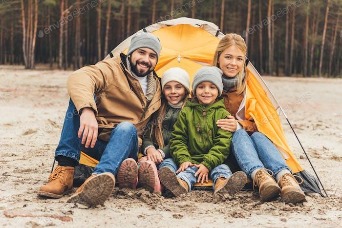 hermosa familia joven sentado junto a la tienda de campaña