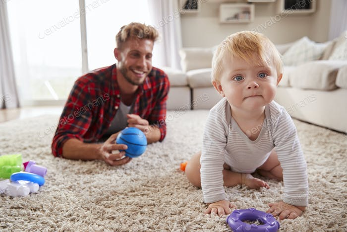Young father lying on floor playing with toddler son at home
